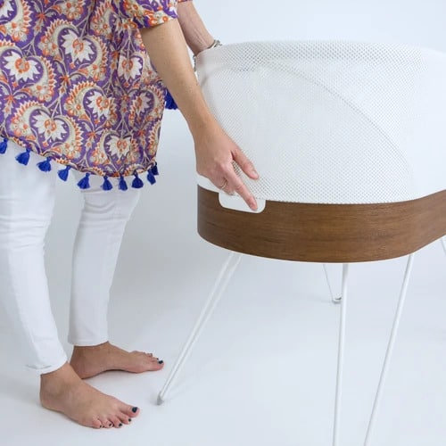 mom holding snoo smart bassinet